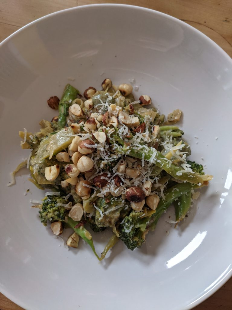 A white dish serving Creamy broccoli and leek gnocchi with hazelnuts.