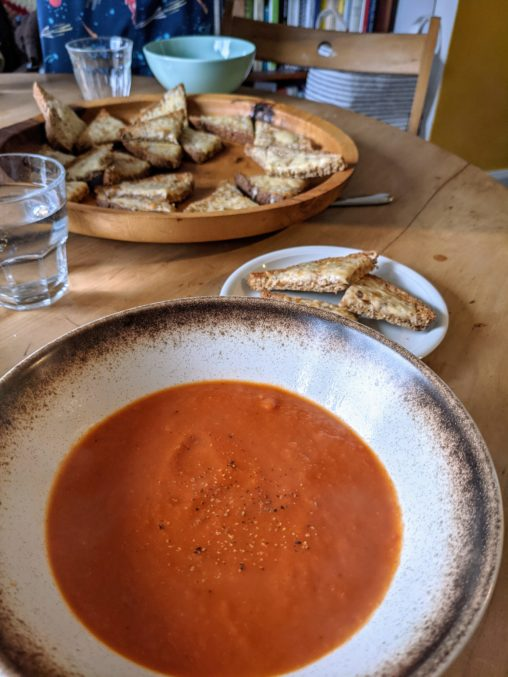 A pine table set with a dish of cheese on toast and a bowl of homemade tomato soup