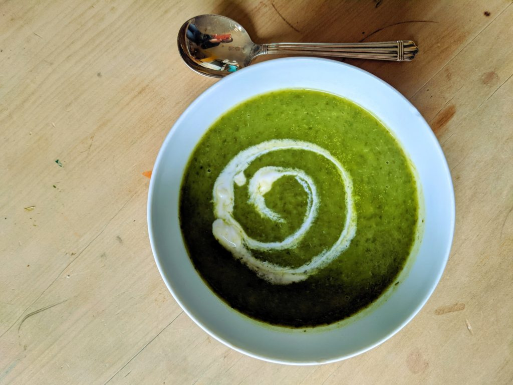 A white soup bowl on a pine table set with bright green Potato and Wild Garlic Soup finished with a swirl of creme fraiche