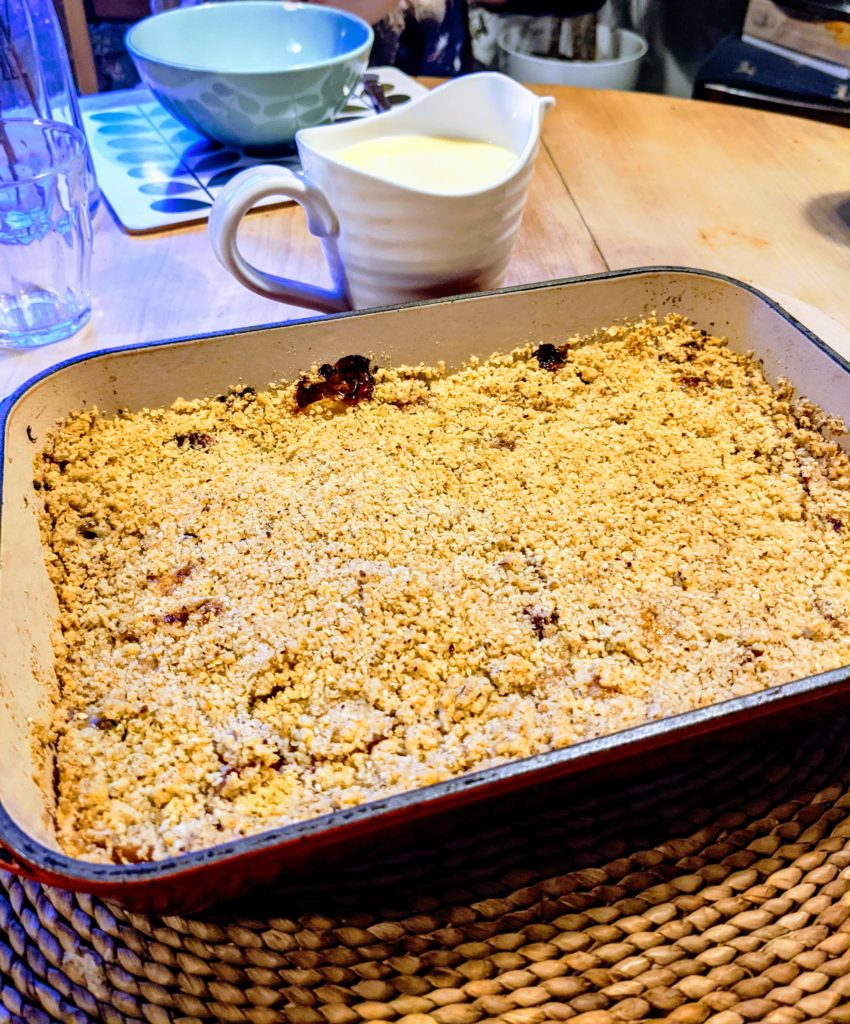 An oven baking dish set on a dining table filled with rhubarb crumble with a white jug of cream