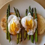 A white plate set with toasted bread, griddle roasted asparagus and poached eggs