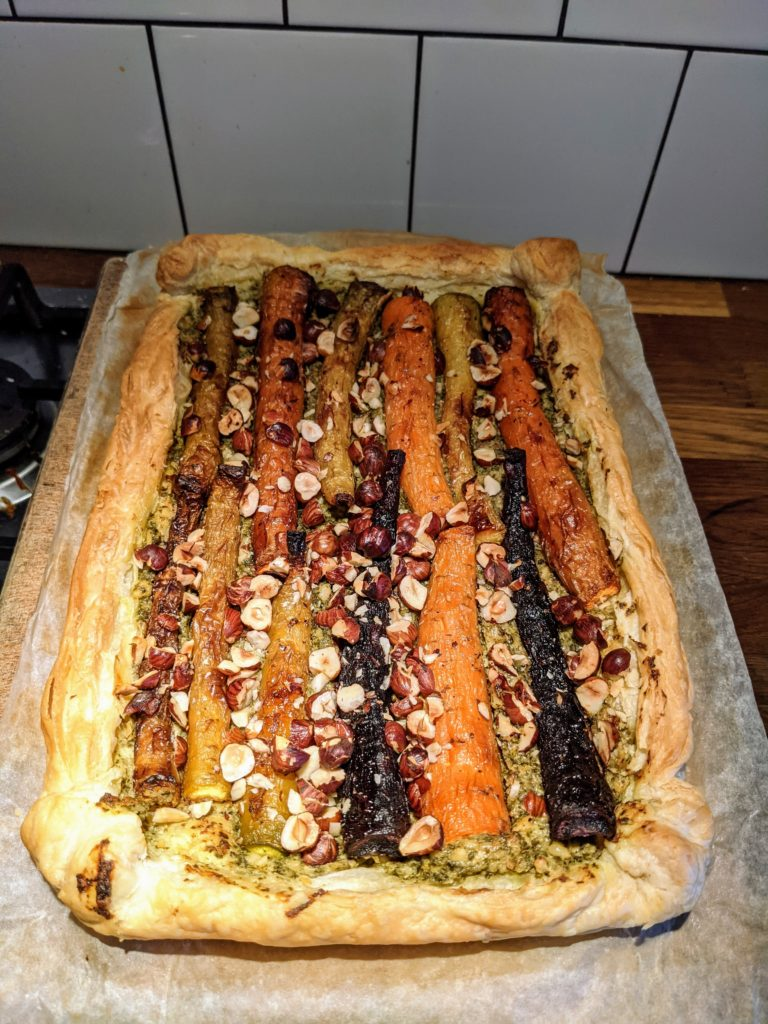 A wax cooking parchment on a cooking tray set with a baked puff pastry carrot and hazle nut tart