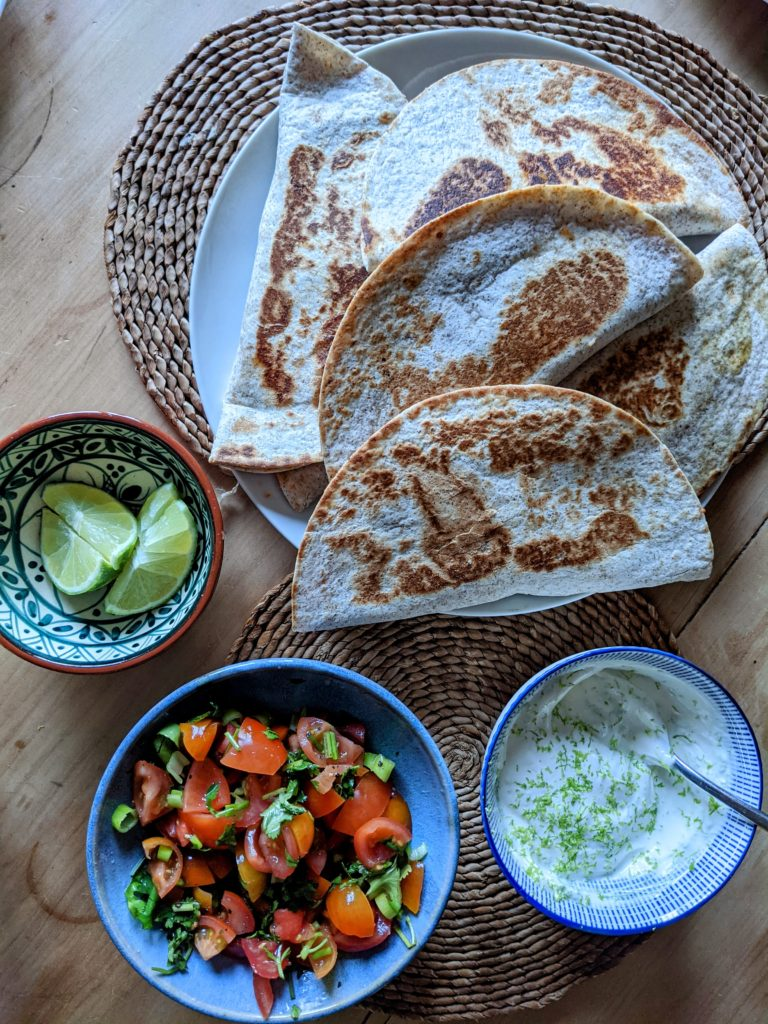 A table set with blue dishes serving salad, lime sour cream dip, quesadillas and lime quarters