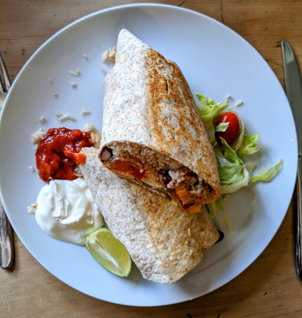 A white plate served with a wholegrain breakfast burrito with salsa, a wedge of lime and sour cream.