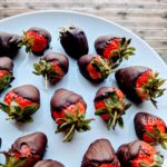 A white plate with chocolate dipped fresh strawberries.