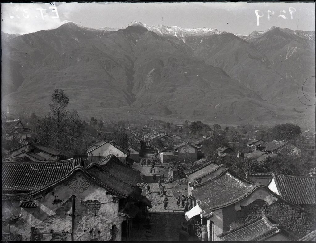 Black and white photograph showing a street in the Chinese town of Dali, with the huge Cangshan mountain range towering in the distance.