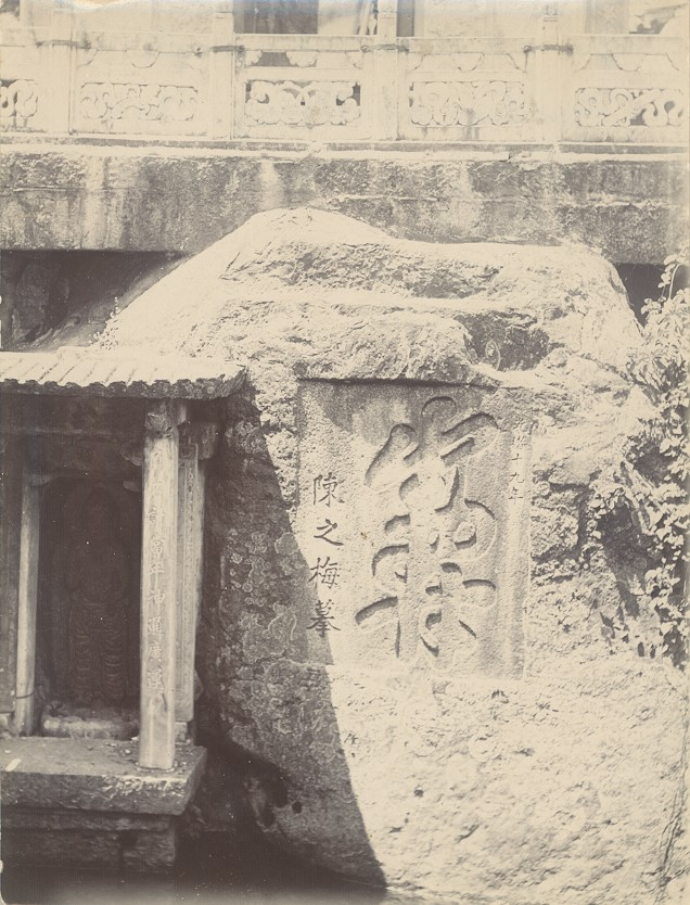 Black and white photograph showing Chinese characters engraved onto a large stone, a statue of the Goddess of Mercy is on the left in an alcove.