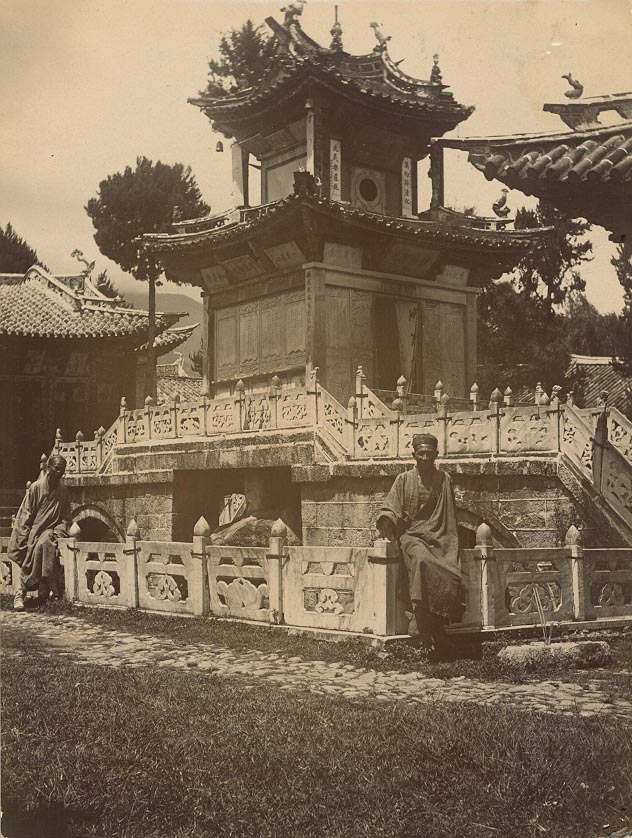 Black and white image of two Chinese gentlemen sitting on a carved stone wall in front of a temple built over a rock in a pond at the Temple of the Goddess of Mercy.