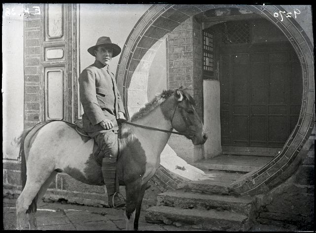 Black and white photograph of George Forrest sitting astride a pony with the circular moongate of the China Inland Mission of the town of Dali in the background.