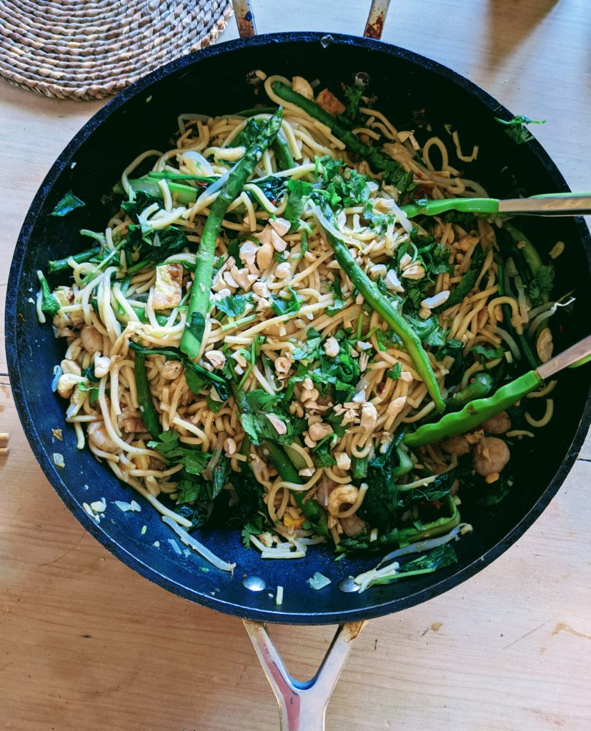 Wide Cooking Pan with freshly cooked noodles and green vegetables ready to serve