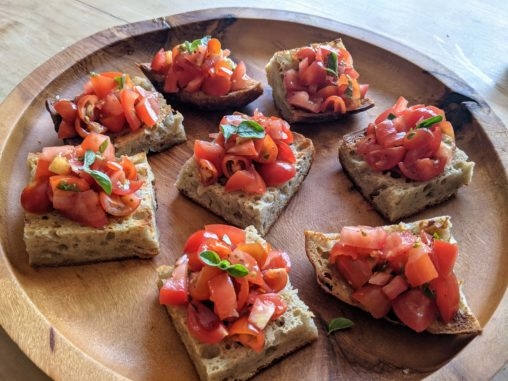 A wooden platter set with a number of small squares of tomato bruschetta