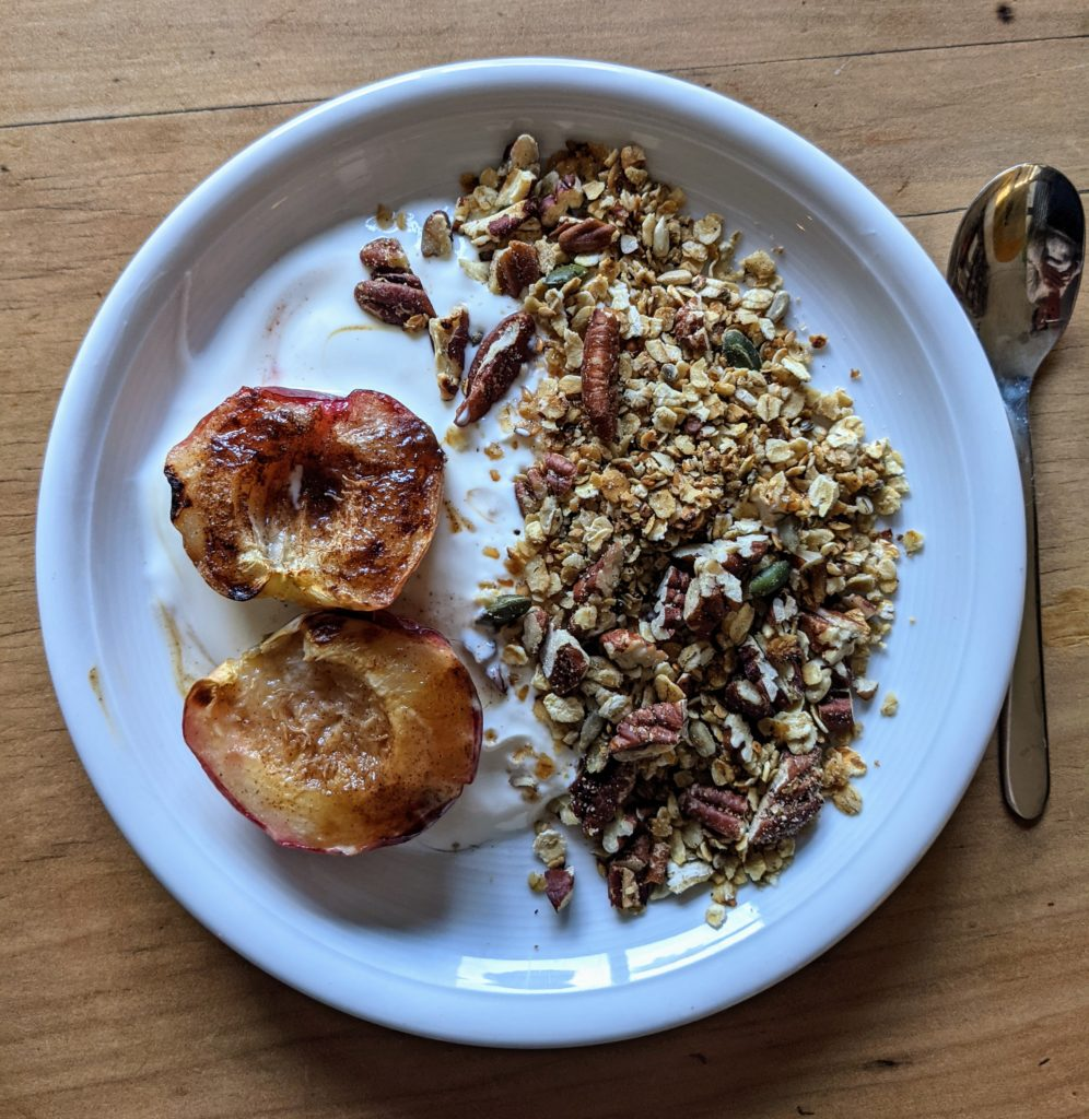 A white china platter serving grilled nectarines with honey yogurt and pecan crumble on a pine table.