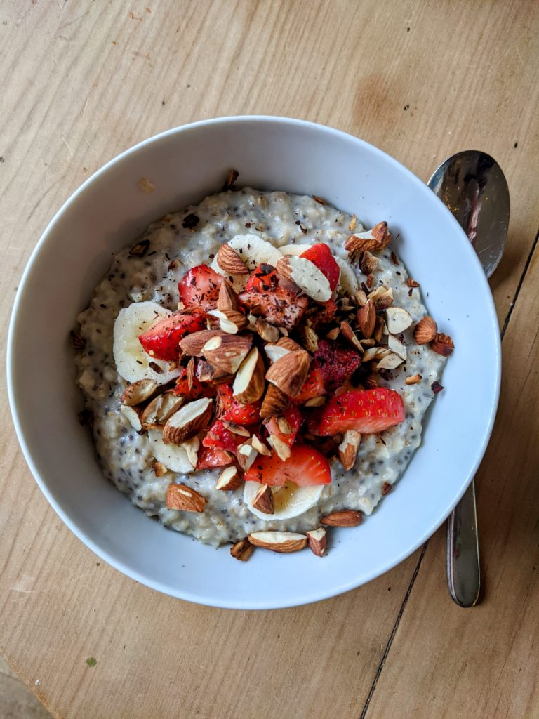 A white china bowl of oat and chia porridge with strawberries and almonds set on a pine table.