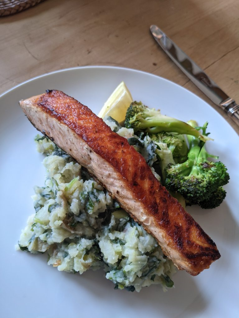 A white china plate of Salmon fillets with kale colcannon.