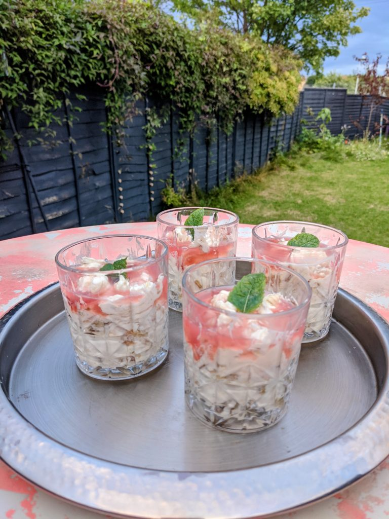 A silver tray on a pink table in the garden, served with 4 glasses filled with rhubarb fool and topped with a bright green mint leaf.
