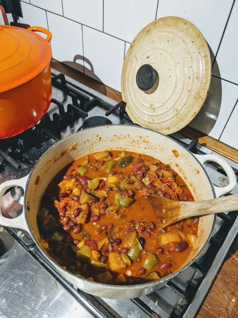 A large cooking pot on the stove with aubergine and black bean chilli and a large wooden spoon.