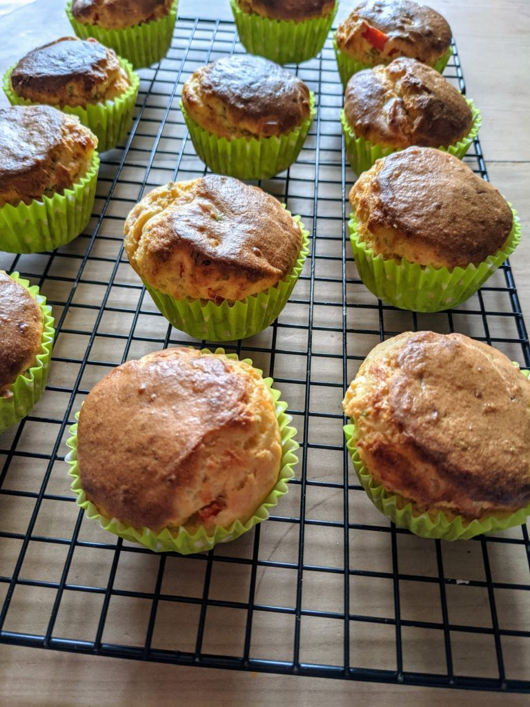 A cooling tray of baked muffins in lime green cases.