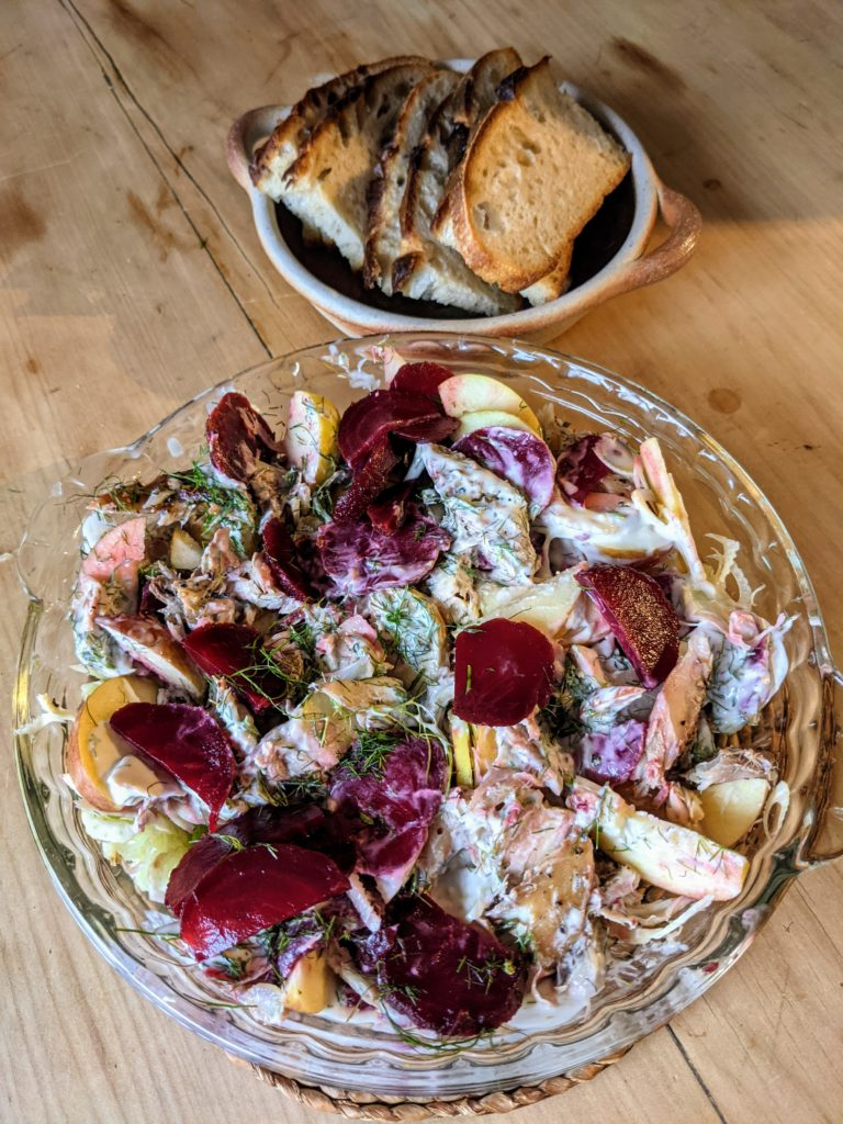 A clear glass dish set on a pine table with mackerel, fennel, beetroot and apple salad served in it.